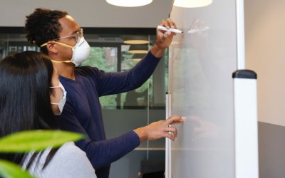man and woman coworkers writing on white board wellbeing statistics on fulfilment at work