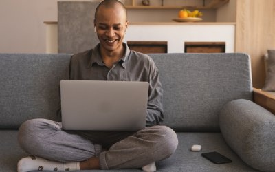 man crossed legs on sofa smiling psychological safety at work from home